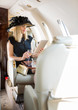 Woman With Drink Using Digital Tablet In Private Jet
