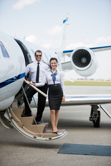 Confident Airhostess And Pilot Standing On Private Jet's Ladder