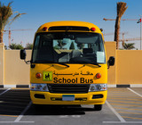 A front on view of a yellow Arabic school bus