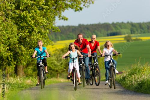 canvas print picture Familie fährt Fahrrad im Sommer