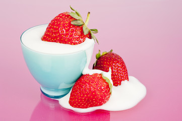Three strawberries in blue cup on pink background