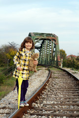 beautiful little girl standing on railroad