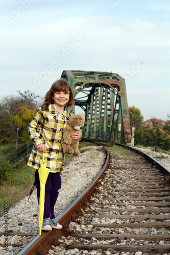 beautiful little girl standing on railroad