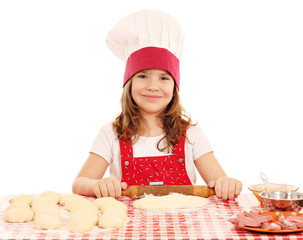 little girl kneading dough with rolling pin