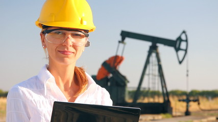 Smiling female engineer in an oilfield
