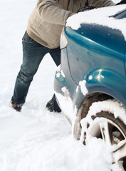closeup of man pushing car stuck in snow