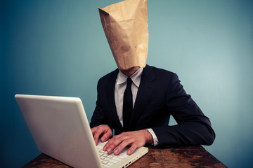 Businessman with bag over head working on computer