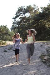 Tochter und Mutter rennen durch die Dünen