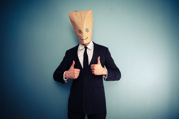 Businessman with bag over head giving two thumbs up