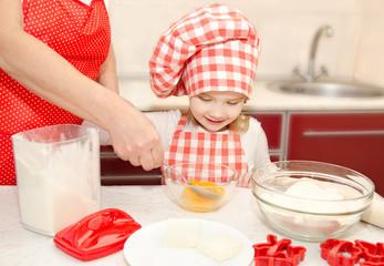 Little girl and grandmother stirrring cookie doug