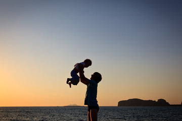 father and son silhouettes at the beach