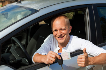 junger erwachsener mann im neuen auto mit schlüssel lachend