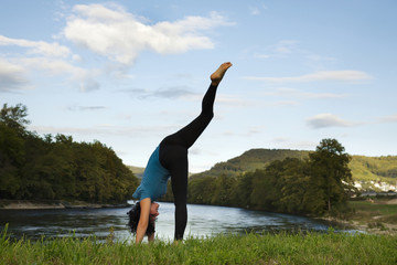 Active woman practicing yoga outdoor.
