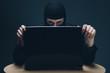 Hacker stealing data off a laptop computer
