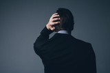 Businessman standing with his hand to his head
