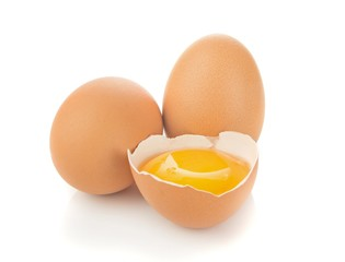 A separated egg yolk and eggs on a white background