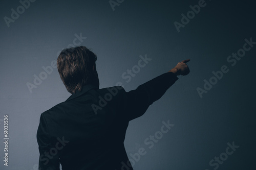 Businessman standing pointing ahead