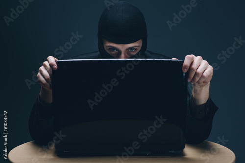 Hacker stealing data off a laptop computer