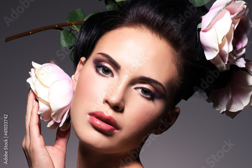 Closeup portrait of beautiful young woman with pink flowers in h