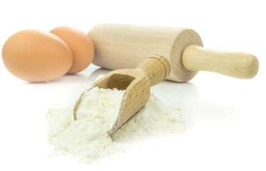 Flour and eggs with baking utensils on white background
