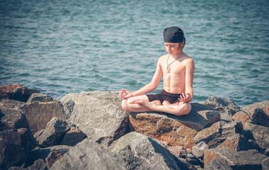 Young boy practising yoga on beach