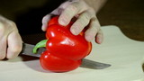 The man cuts red pepper