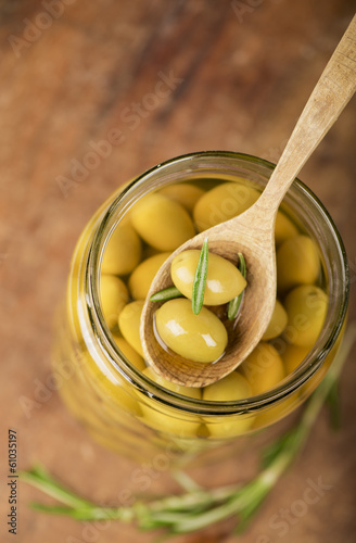 Close up green olives in bank, rosemary on a wooden background