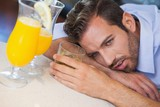 Drunk businessman slumped on bar beside cocktail