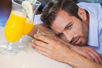 Drunk businessman slumped on bar beside cocktail