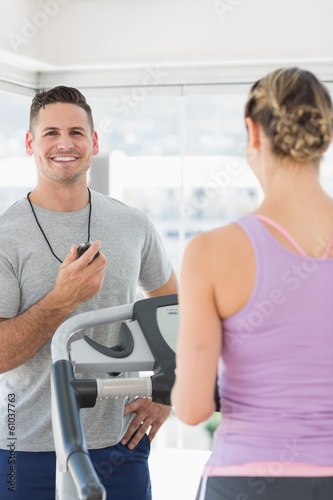 Fitness trainer holding stopwatch with woman exercising