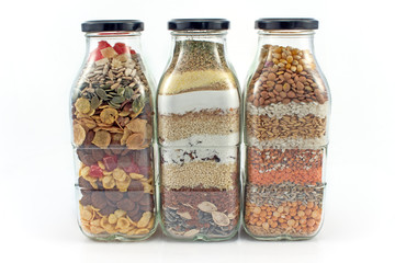 Decorative glass bottles with seeds isolated on white