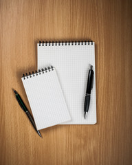 Notebook with pen on wood background