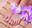 Pedicure with pink orchid flowers on bamboo mat. Beautiful