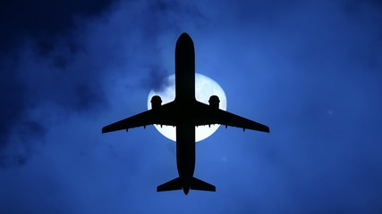 Plane flying by the moon