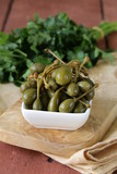 Pickled capers in bowl on a wooden table