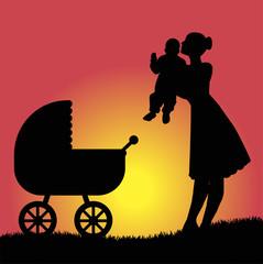 mamma con figlio e carrozzina a passeggio nel parco