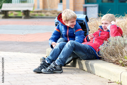 Teenager school boys twin brothers calling on mobile phone
