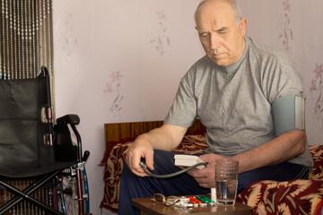 Senior handicapped man taking his blood pressure