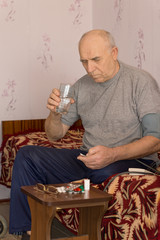 Unwell senior man taking medication