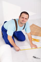 Man laying laminate floor at home
