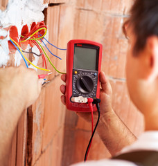 Electrician hands with multimeter - closeup