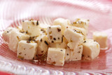 Spiced feta cheese on red table and glass dish