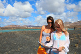 Two young attractive women with land map in summer holiday outdo
