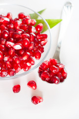 Ripe pomegranate seeds on a glass plate.