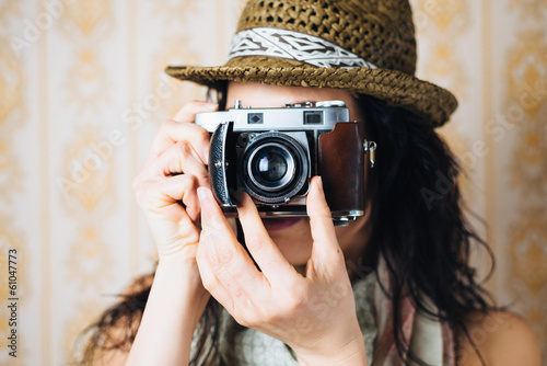 Female hipster taking photo with retro camera