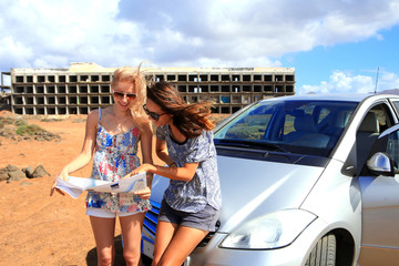 Two young women with car look at road map with old building in b
