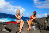 two girls taking photo on the beach in summer holidays and vacat