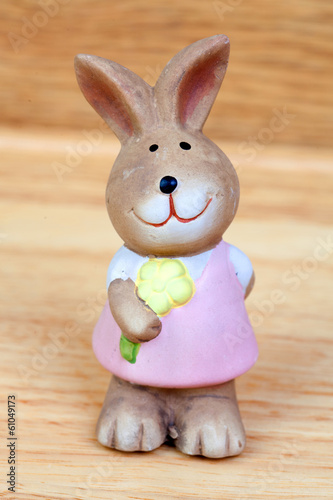Easter time. Ceramic rabbit with a flower