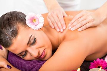 junge frau entspannt bei einer rücken massage im salon