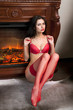 girl in red underwear sits near fireplace